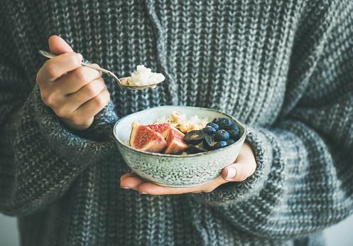 Woman In Woolen Sweater Eating Rice Coconut Porridge - Fotografie stock e altre immagini di A maglia