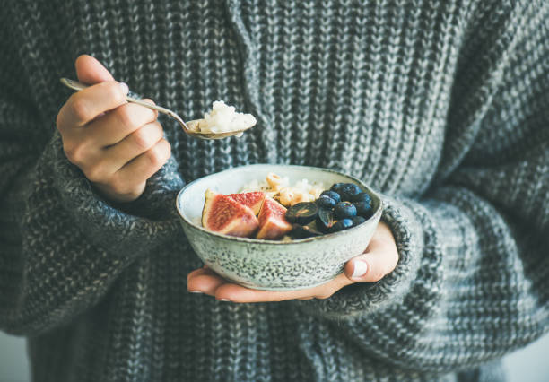 woman in woolen sweater eating rice coconut porridge - porridge foto e immagini stock