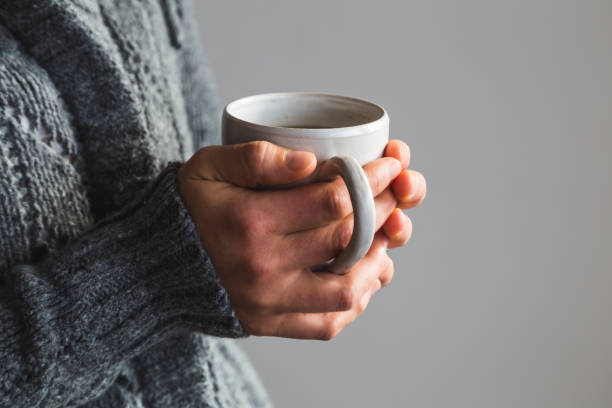 woman in woolly gray sweater holding warm cup of tea - jumping zdjęcia i obrazy z banku zdjęć