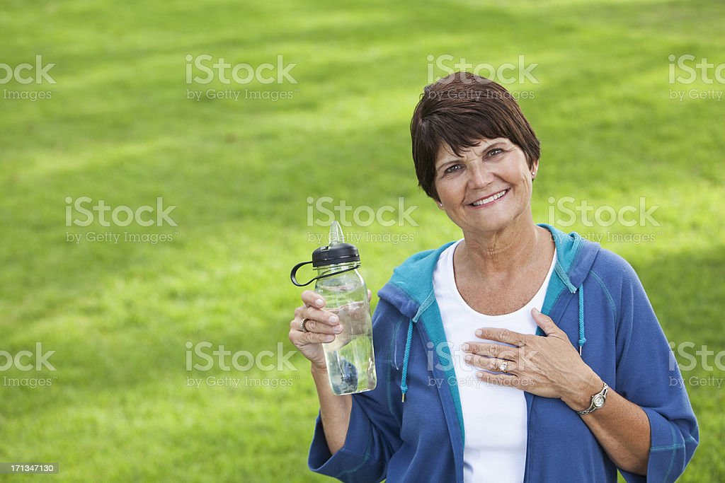 Woman in workout clothes holding water bottle stock photo