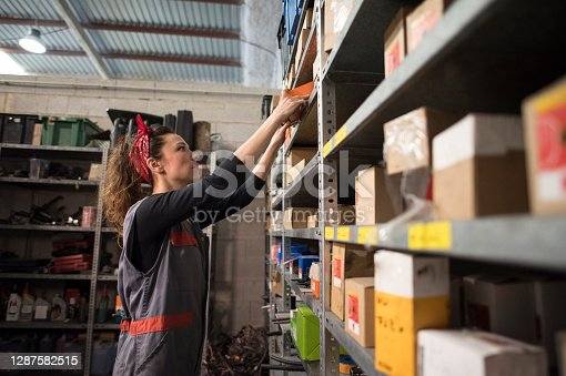 Woman in workshop looks for spare parts and pieces in different boxes placed on the shelves