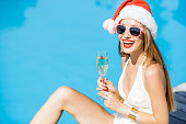 Young woman in Christmas hat and swimsuit celebrating New Year with glass of wine at the swimming pool. Winter vacation concept