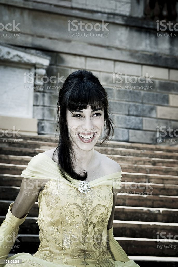 Woman in Yellow Ball Gown Sitting on Stairs stock photo