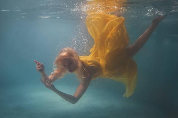 woman in yellow dress under water. - meerjungfrau kleid stock-fotos und bilder