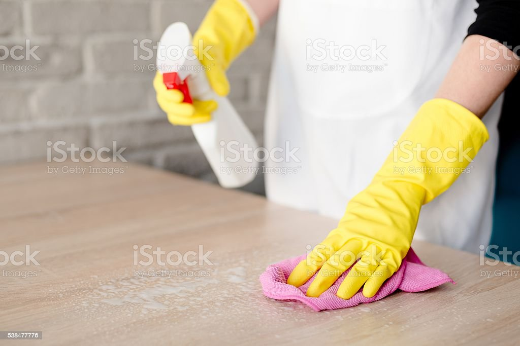 Woman in yellow rubber gloves cleaning table stock photo