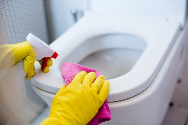 Woman in yellow rubber gloves cleaning toilet stock photo