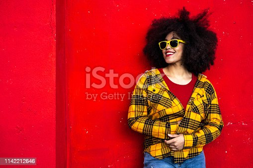 istock Woman in yellow shirt and yellow sunglasses 1142212646