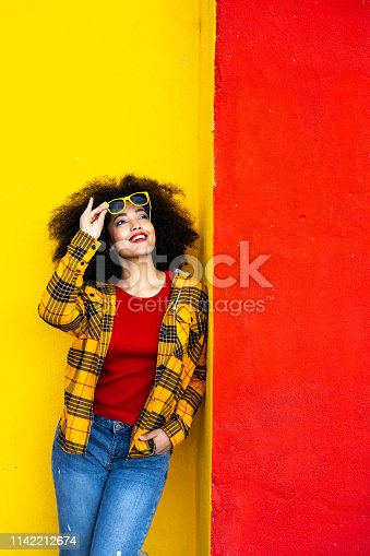 istock Woman in yellow shirt and yellow sunglasses 1142212674