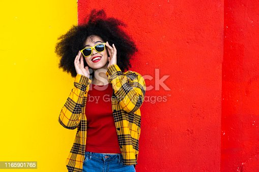 Woman wearing yellow shirt, red blouse and yellow sunglasses in front of red and yellow background