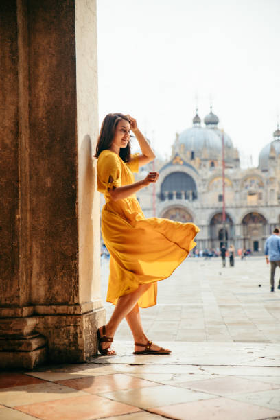 woman in yellow sundress at saint marco piazza stock photo