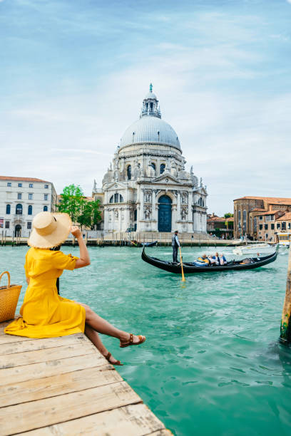woman in yellow sundress sitting on pier with view of grand canal stock photo