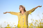 A woman lifting her arms in a field of yellow wildflowers