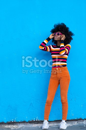 Woman wearing yellow vest and sunglasses in front of blue background