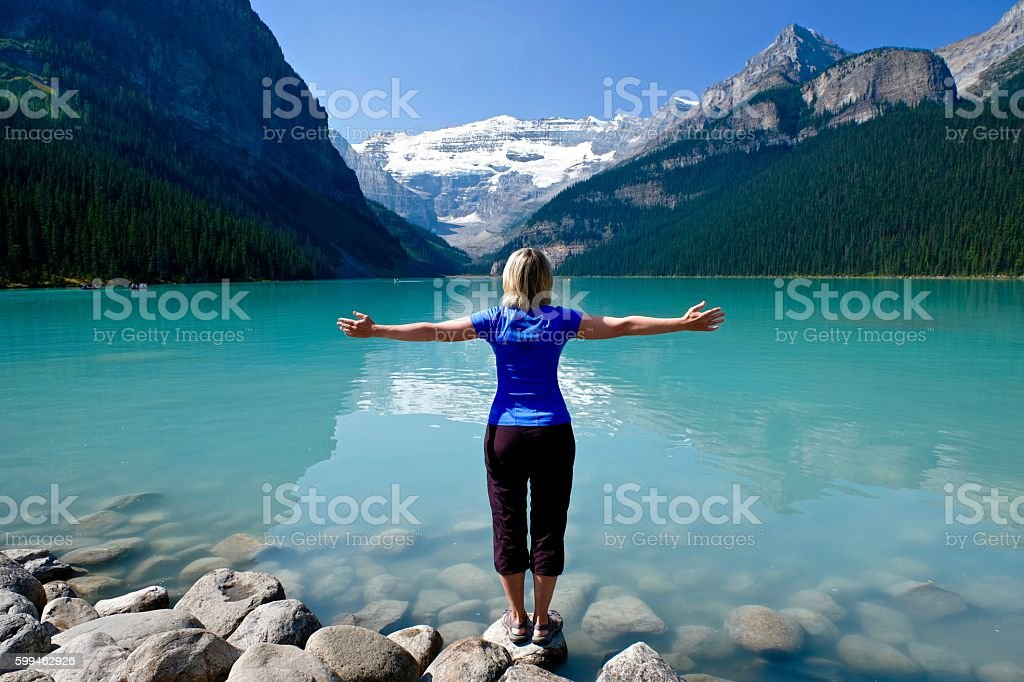 Woman in yoga pose meditating by water. stock photo