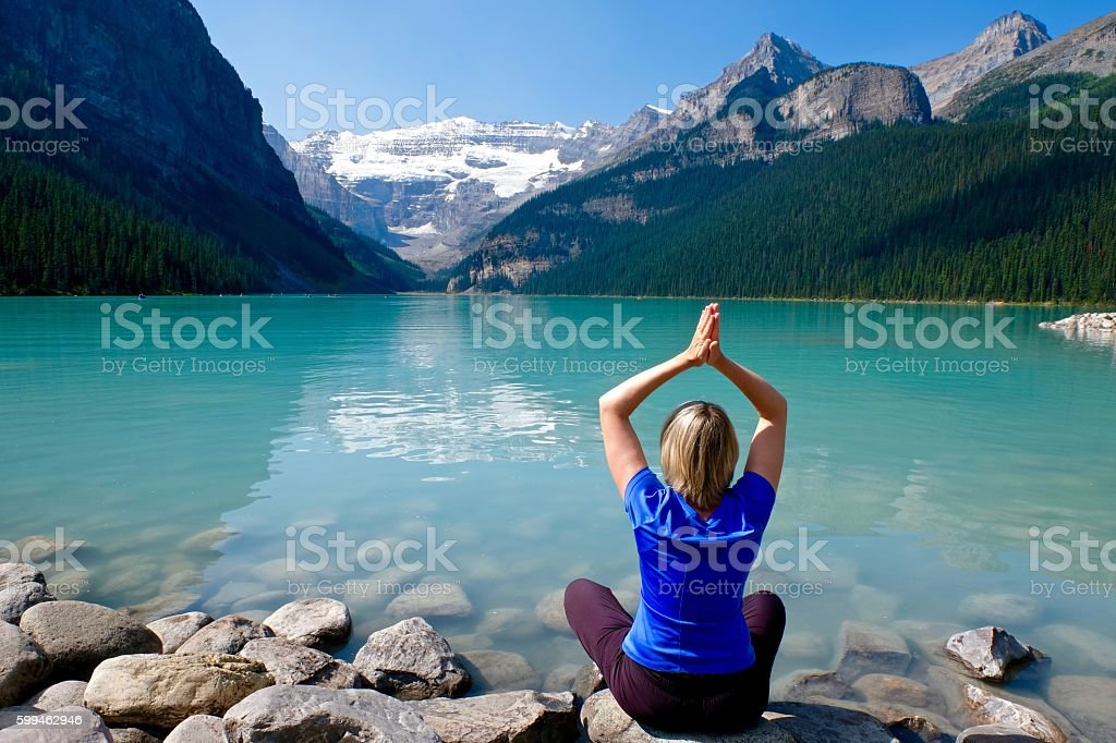 Woman in yoga pose meditating by water. – Foto