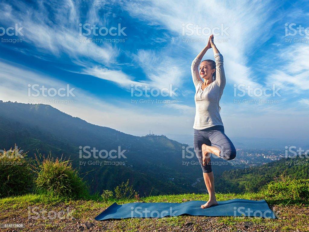 Woman in yoga Vrikshasana tree pose outdoors stock photo