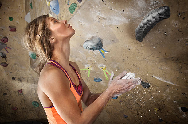 Woman Indoor Climbing Removes Chalk From Hand stock photo
