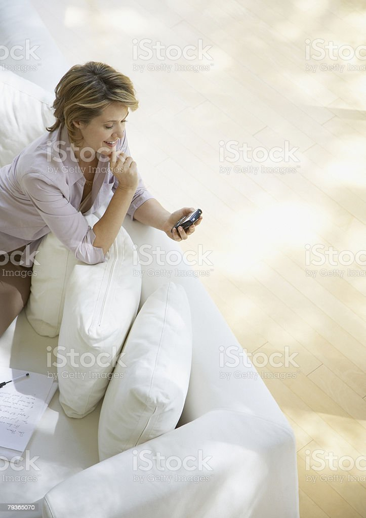 Woman indoors using her mobile phone royalty-free stock photo