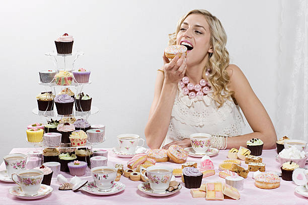 Woman indulging in doughnuts and cakes stock photo