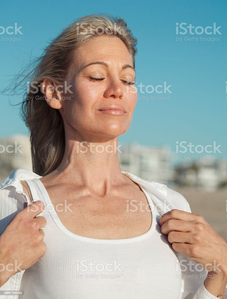 Woman inhaling fresh air at the beach stock photo