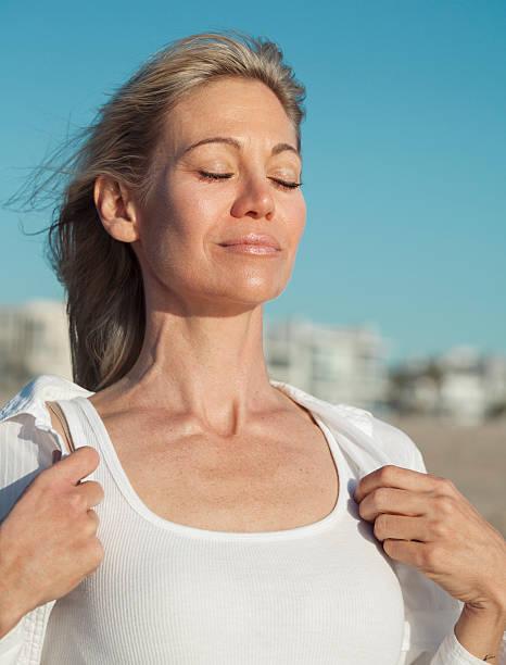 Woman inhaling fresh air at the beach stock photo
