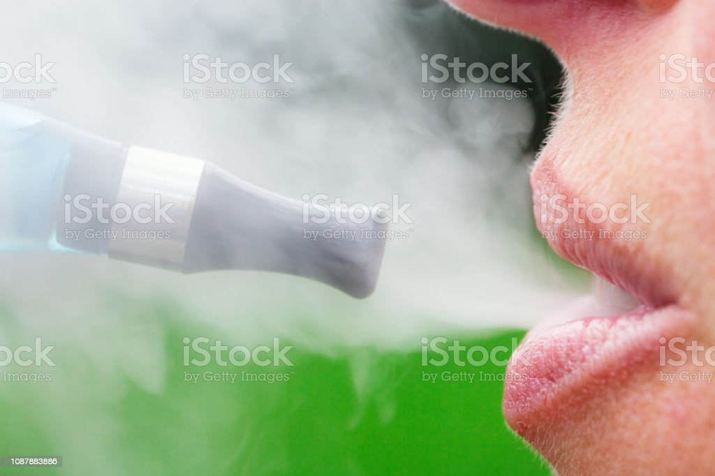 woman inhaling from an electronic cigarette - Foto stock royalty-free di Adulto