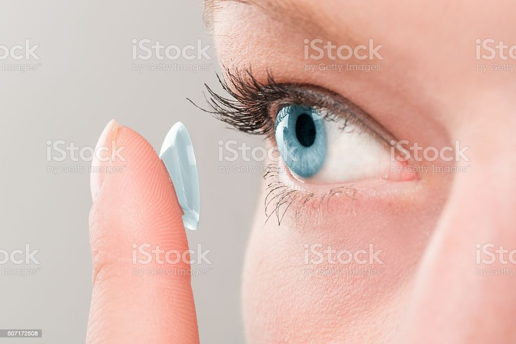 Woman inserting a contact lens in eye. stock photo