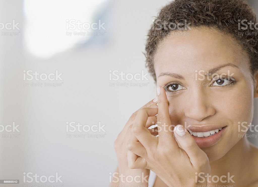 Woman inserting contact lens stock photo