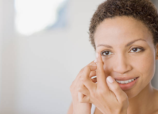 Woman inserting contact lens  inserting stock pictures, royalty-free photos & images