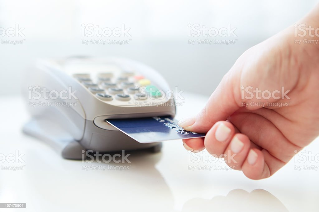 Woman inserting her card into machine to pay by credit stock photo