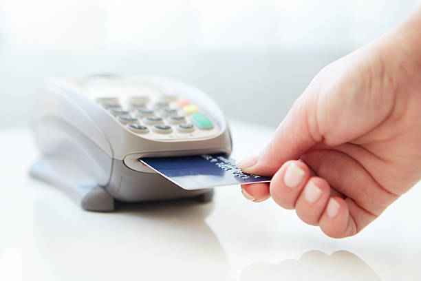 Woman inserting her card into machine to pay by credit Woman pay by credit card in store smart card stock pictures, royalty-free photos & images