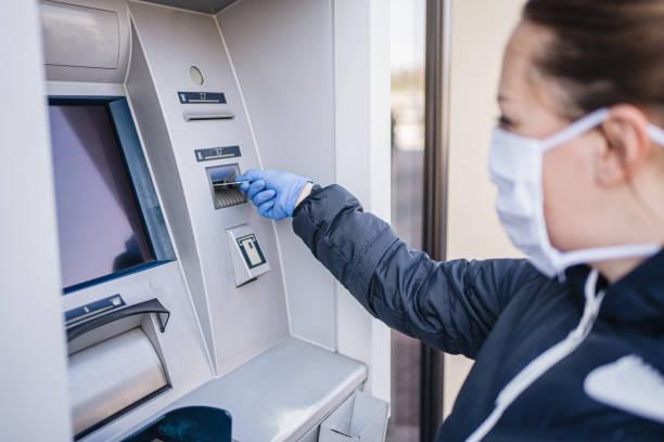 Frau legt ihre Kreditkarte während einer Pandemie in einen Geldautomaten ein – Foto