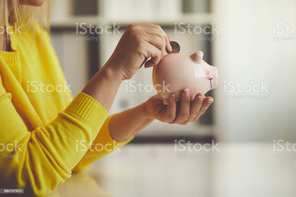 Woman inserts a coin into a piggy bank stock photo