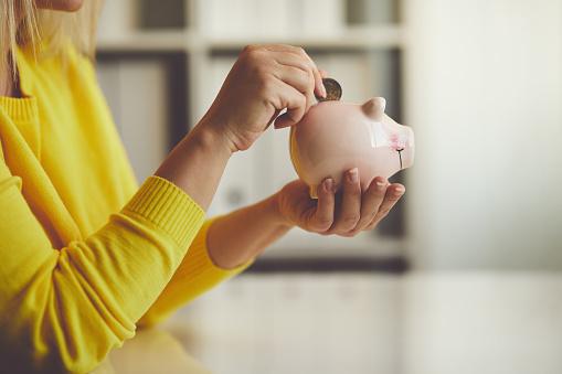 Mujer Inserta Una Moneda En Una Alcancía Foto de stock y más banco de imágenes de Actividades bancarias