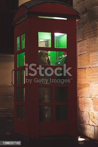 Single Woman inside of Red Phone Booth Sydney Night