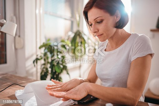 Woman wearing white shirt inspecting her freshly painted nails