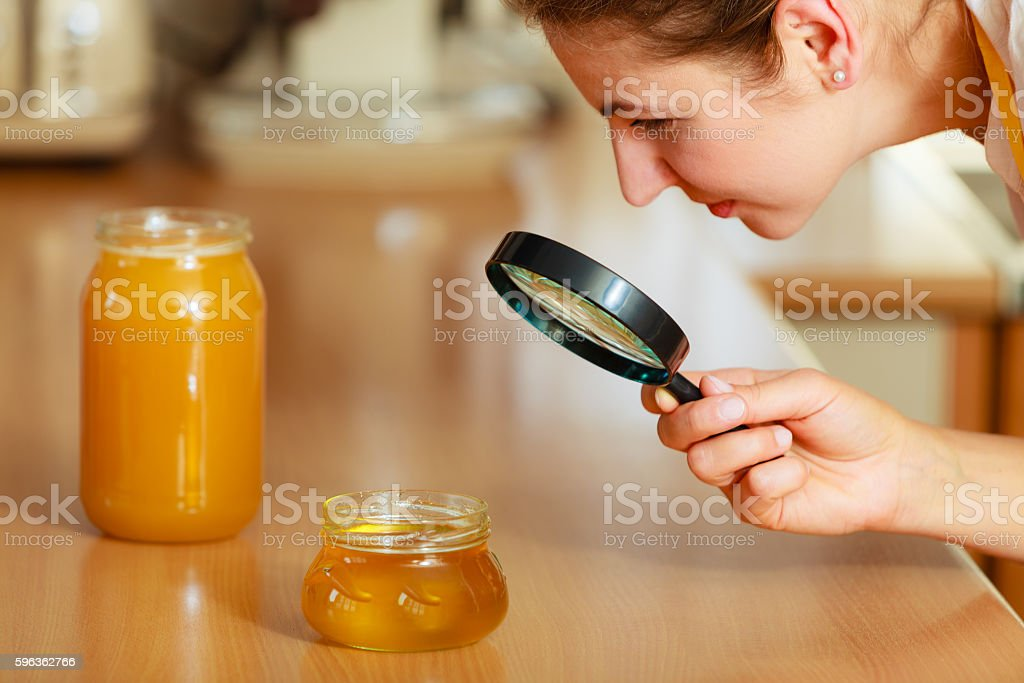 Woman inspecting honey with magnifying glass. royalty-free stock photo