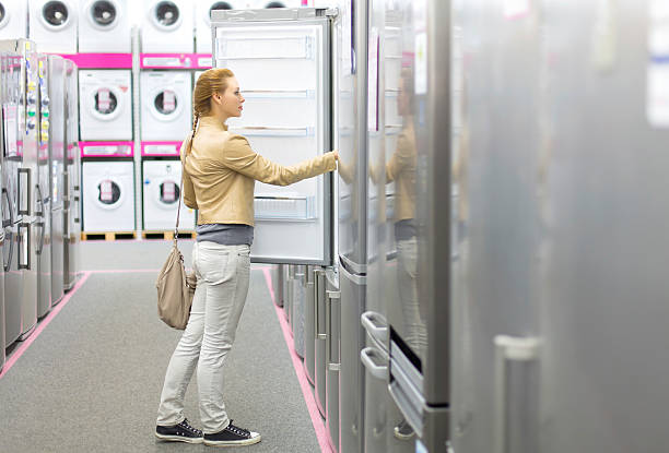 Woman inspects refrigerator space inside appliance store stock photo