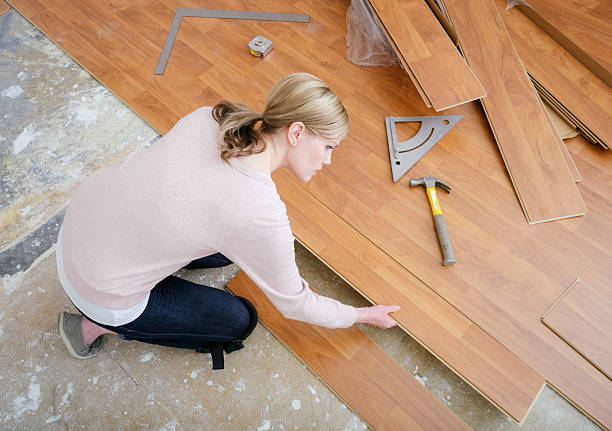 Woman Installing Laminate Flooring stock photo