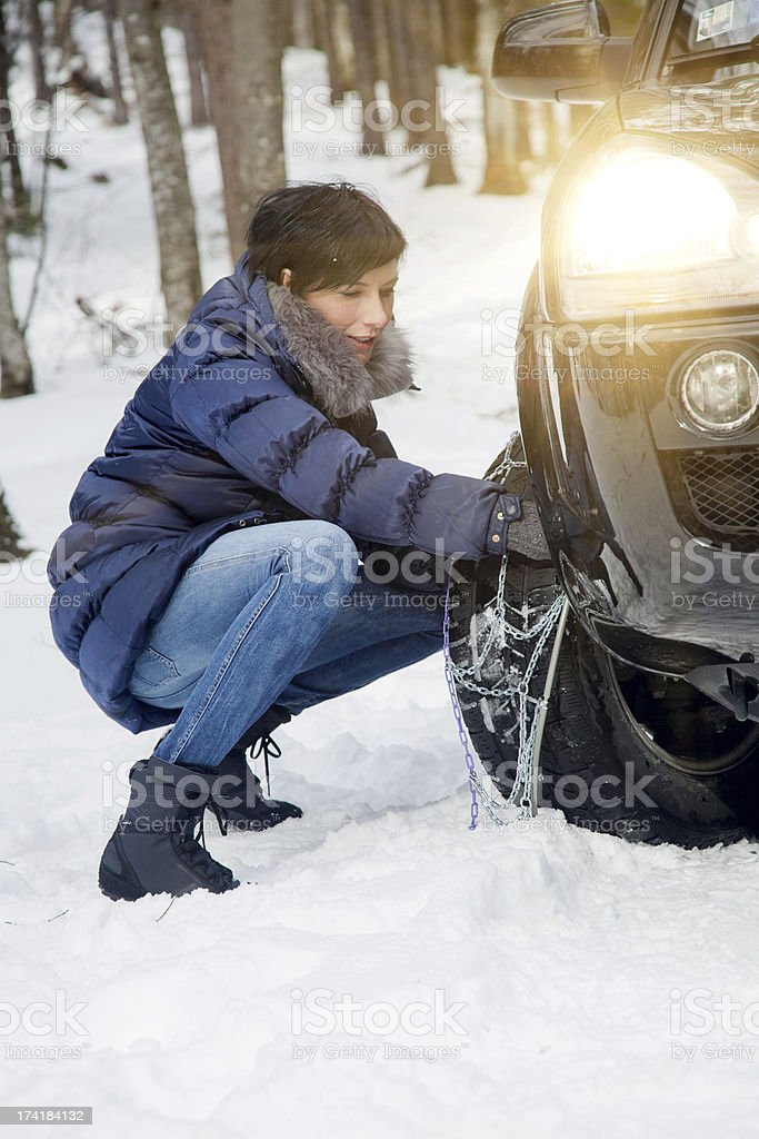 Woman installing snow chains stock photo