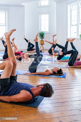 1069872470 istock photo Woman instructing students in yoga studio 1145392575