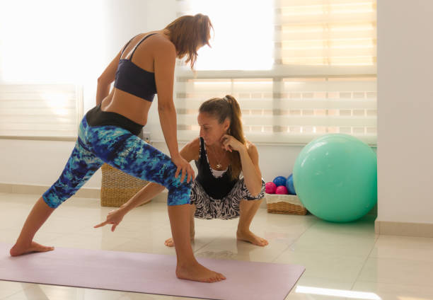 Woman instructor teaching yoga to young girl in bright studio Female yogis in colorful sport wear. Teacher pointing at student foot. Profession, pilates balls, props, training class concepts yoga instructor stock pictures, royalty-free photos & images