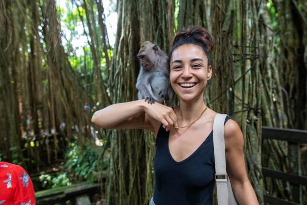 mulher, interagindo com um macaco em bali, indonésia - macaco - fotografias e filmes do acervo