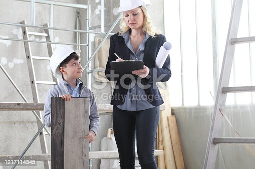 527687520 istock photo woman interior designer or architect mom with her son at work, they choose how to furnish the house, inside the construction site 1217114345