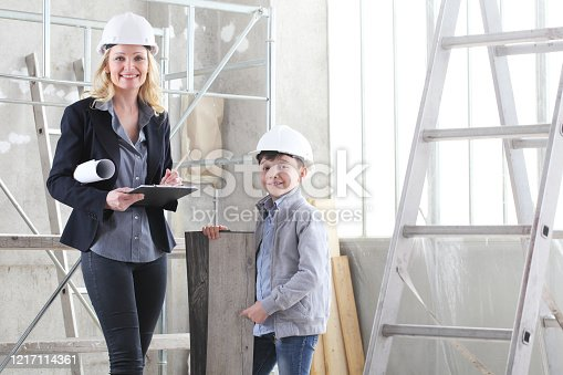 527687520 istock photo woman interior designer or architect mom with her son at work, they choose how to furnish the house, inside the construction site 1217114361
