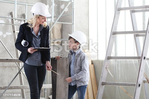 527687520 istock photo woman interior designer or architect mom with her son at work, they choose how to furnish the house, inside the construction site 1217114526