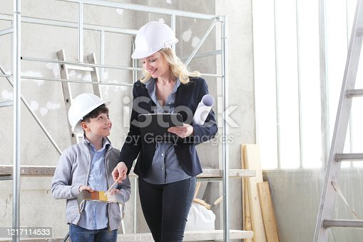 527687520 istock photo woman interior designer or architect mom with her son at work,, they choose colors from color swatch to decorate the house, inside the building site 1217114533