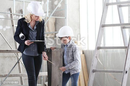 527687520 istock photo woman interior designer or architect mom with her son at work, they choose how to furnish the house, inside the construction site 1217115183