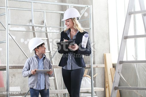 527687520 istock photo woman interior designer or architect mom with her son they work together on the construction of the house, inside the building site 1217114347