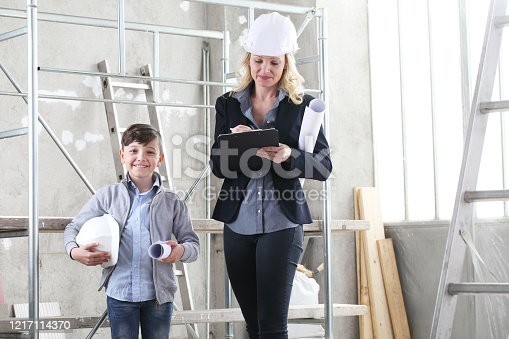 527687520 istock photo woman interior designer or architect mom with her son they work together on the construction of the house, inside the building site 1217114370